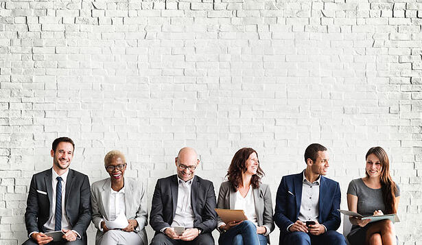 Diverse-business-men-and-women-sitting-in-front-of-white-brick-wall-smiling
