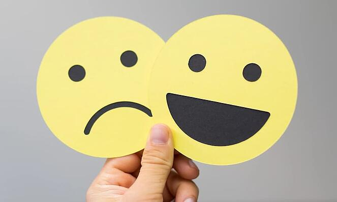Person holding two emoji cut-outs, one happy and one sad