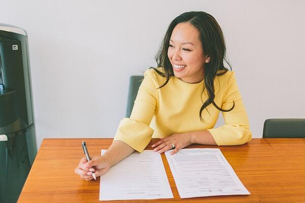 Woman working on paperwork and smiling