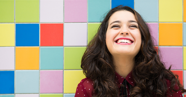 Woman smiling in front of a colorful wall