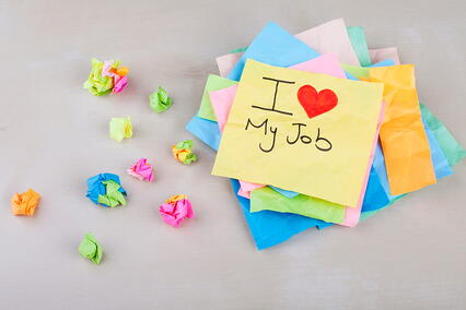 """Sticky note pile that says """"I love my job"""" on top"""