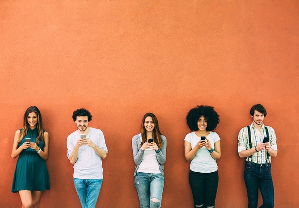 Group of people on their phones leaning against orange wall